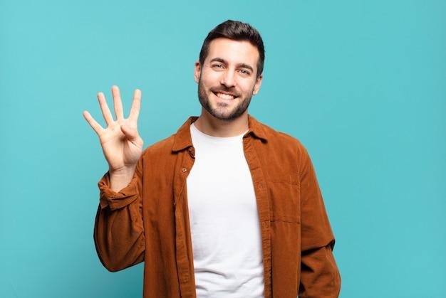 Bel homme blond adulte souriant et semblant amical, montrant le numéro quatre ou quatrième avec la main en avant, compte à rebours
