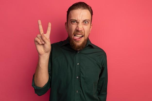 Bel homme blond en colère sort la langue et les gestes signe de la main de la victoire isolé sur le mur rose