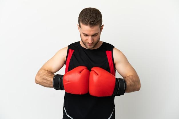 Bel homme blond sur fond blanc isolé avec des gants de boxe