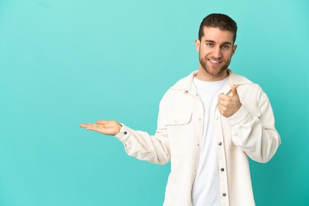 Bel homme blond sur fond bleu isolé tenant un espace de copie imaginaire sur la paume pour insérer une annonce et avec les pouces vers le haut