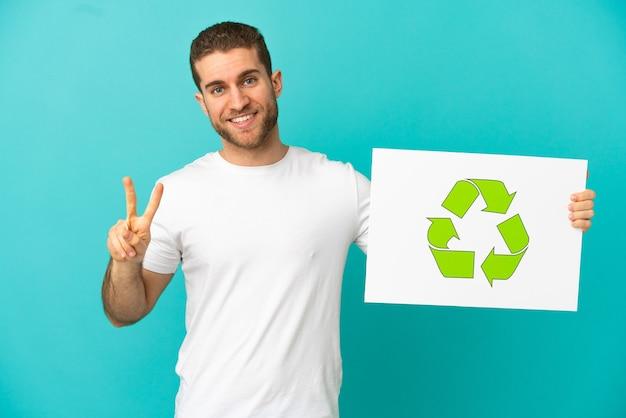 Bel homme blond sur fond bleu isolé tenant une pancarte avec l'icône de recyclage et célébrant une victoire