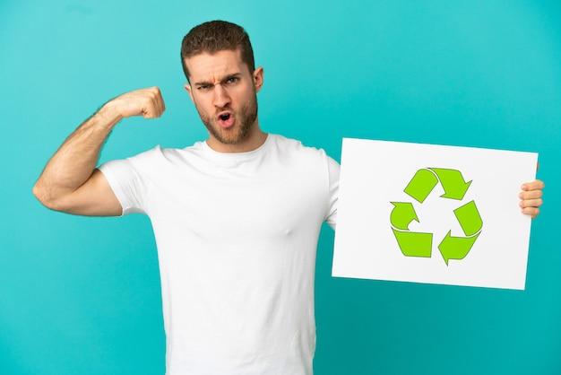 Bel homme blond sur fond bleu isolé tenant une pancarte avec l'icône de recyclage et faisant un geste fort
