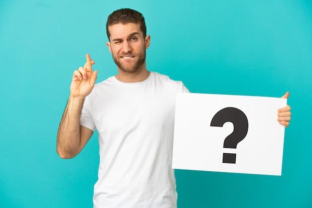 Bel homme blond sur fond bleu isolé tenant une pancarte avec un point d'interrogation avec le croisement des doigts