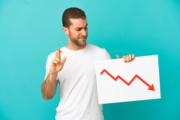 Bel homme blond sur fond bleu isolé tenant une pancarte avec un symbole de flèche de statistiques décroissantes avec le croisement des doigts