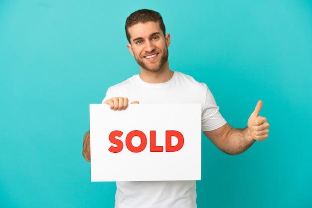 Bel homme blond sur fond bleu isolé tenant une pancarte avec texte vendu avec le pouce vers le haut