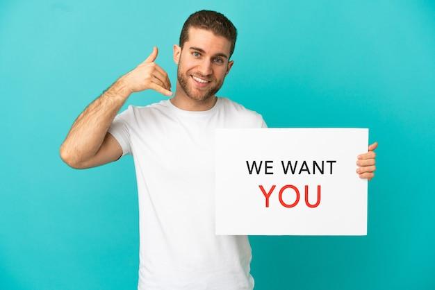Bel homme blond sur fond bleu isolé tenant we want you board et faisant un geste téléphonique