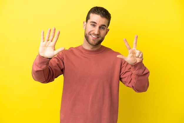 Bel homme blond sur fond jaune isolé comptant huit avec les doigts