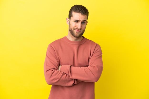 Bel homme blond sur fond jaune isolé se sentir contrarié