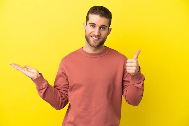 Bel homme blond sur fond jaune isolé tenant un espace de copie imaginaire sur la paume pour insérer une annonce et avec les pouces vers le haut