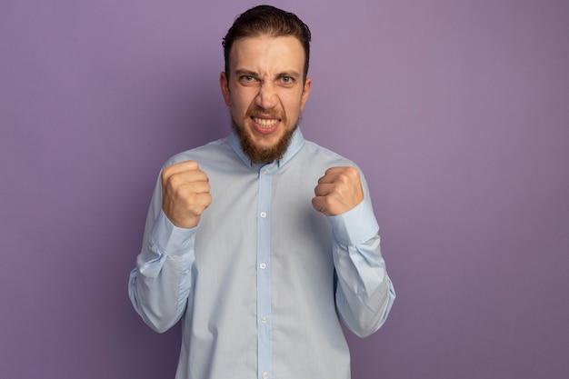 Bel homme blond furieux garde les poings isolés sur un mur violet