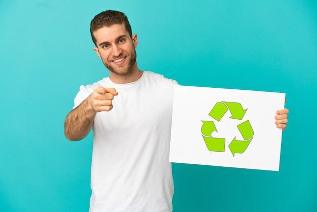 Bel homme blond isolé tenant une pancarte avec icône de recyclage et pointant vers l'avant