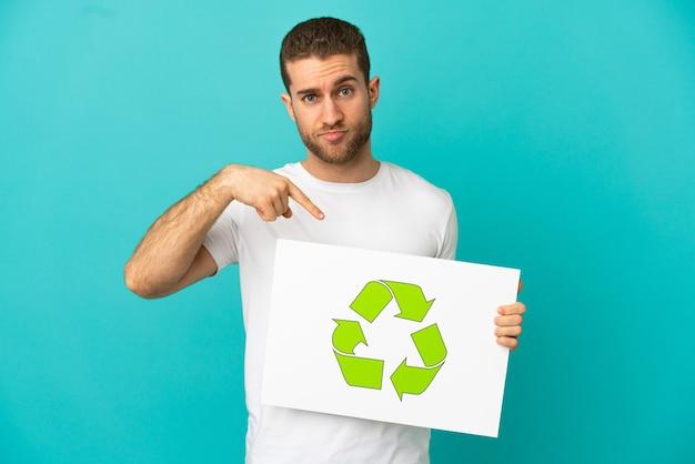 Bel homme blond isolé tenant une pancarte avec l'icône de recyclage et la pointant