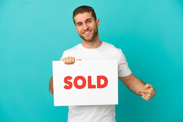 Bel homme blond isolé tenant une pancarte avec le texte vendu et le pointant