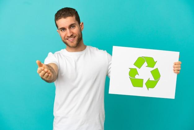 Bel homme blond sur mur bleu isolé tenant une pancarte avec l'icône de recyclage faisant un accord