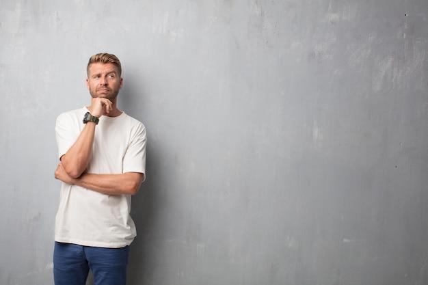 Bel homme blond pensant contre un mur grunge