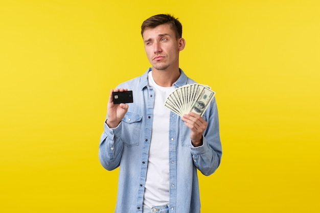 Un bel homme blond sérieux et réfléchi montrant une carte de crédit et de l'argent, détournant les yeux en pensant à comment investir de l'argent, en réfléchissant à ce qu'il faut acheter pendant les achats, debout sur fond jaune.