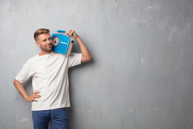 Bel homme blonde écoute la musique avec une radio vintage