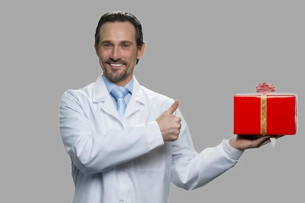 Bel homme en blouse blanche tenant une boîte-cadeau. pharmacien ou assistant de laboratoire montrant la boîte-cadeau et le geste du pouce vers le haut.