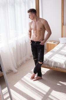 Bel homme en bonne santé aux seins nus pensant au concept de fenêtre à proximité. intérieur de la salle blanche. matin ensoleillé à la maison