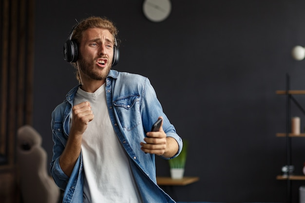 Bel homme bouclé aux cheveux longs avec des écouteurs écoutant de la musique, chantant et dansant. un homme souriant émotionnel drôle avec des écouteurs et un téléphone portable se détend à la maison. profitez de l'écoute de la musique. gestion du stress.