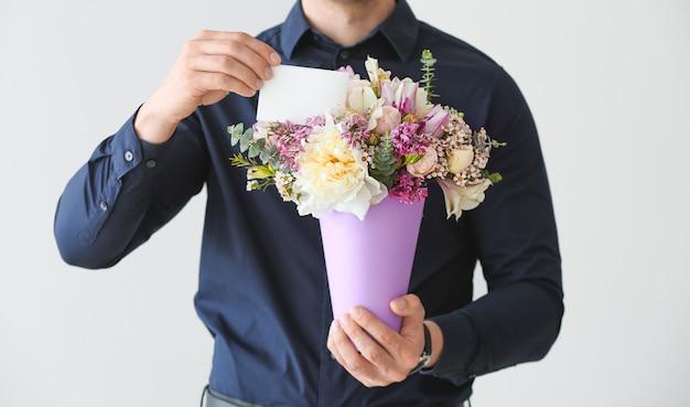 Bel homme avec bouquet de belles fleurs et carte de voeux sur une surface claire