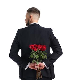 Bel homme avec bouquet de belles fleurs derrière son dos sur une surface blanche