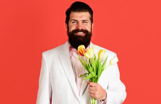 Bel homme avec bouquet de tulipes. homme d'affaires avec des fleurs pour l'anniversaire. la saint-valentin. journée de la femme.
