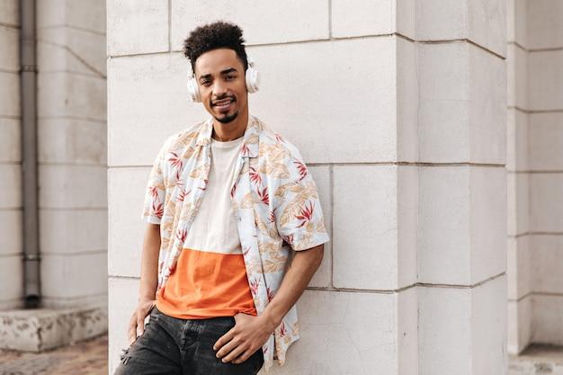 Bel homme brun bouclé à la peau foncée en t-shirt orange, chemise à fleurs et jean noir se penche sur un mur blanc et écoute de la musique dans des écouteurs à l'extérieur