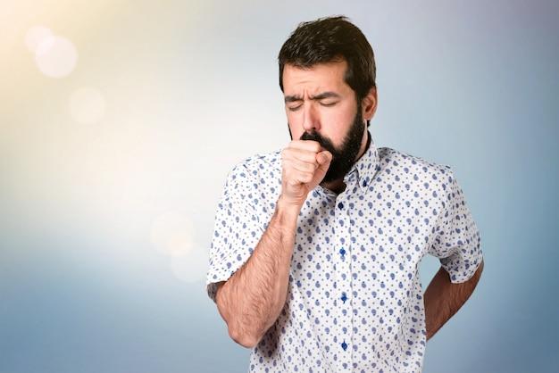 Bel homme brune avec une barbe toussant beaucoup