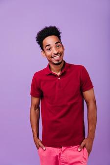 Bel homme brune debout avec les mains dans les poches. portrait intérieur de rire garçon africain optimiste.