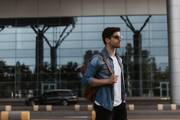 Bel homme brune en veste en jean, t-shirt blanc et pantalon noir pose à l'extérieur