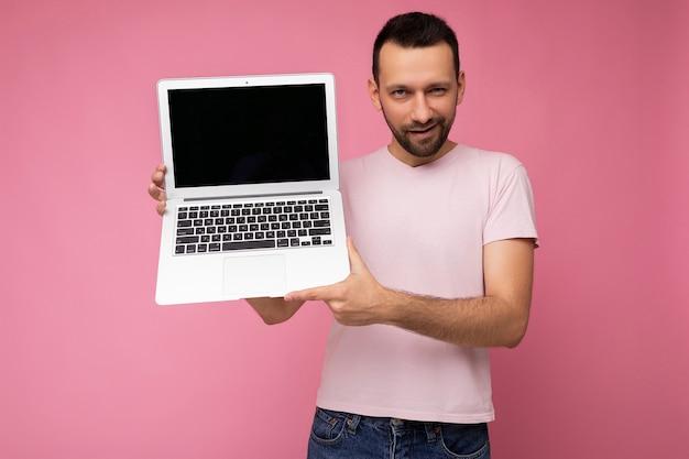 Bel homme brunet souriant et clignotant tenant un ordinateur portable