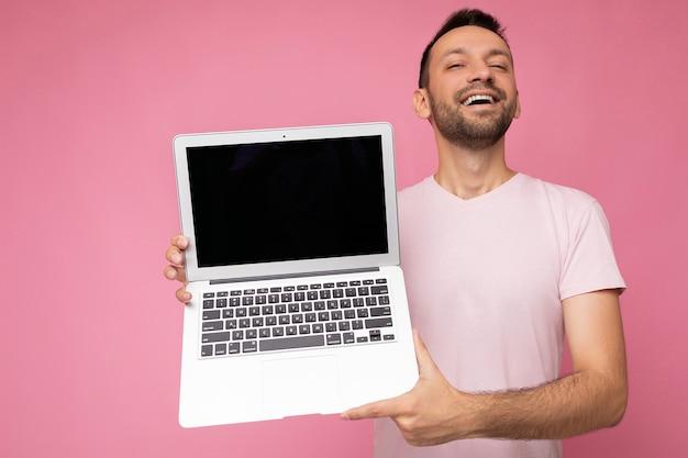 Bel homme brunet souriant tenant un ordinateur portable regardant la caméra