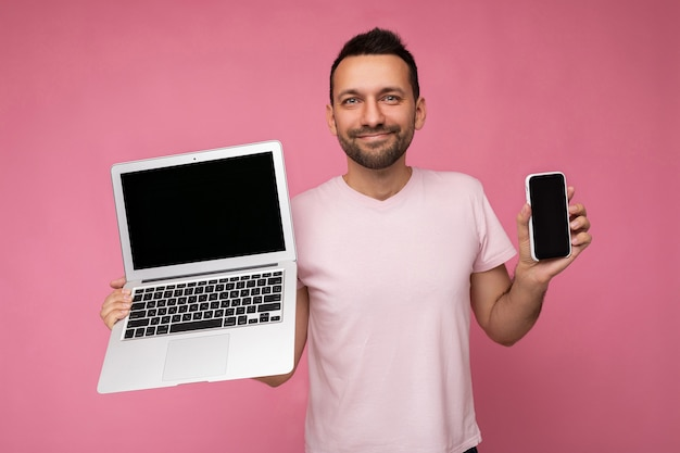 Bel homme brunet souriant tenant un ordinateur portable et un téléphone mobile en regardant la caméra en t-shirt sur fond rose isolé.