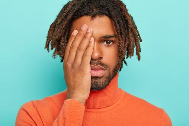 Bel homme cache la moitié du visage avec la paume, regarde sérieusement la caméra, a des dreads sombres, porte un pull à col polon orange, est fatigué après un long travail