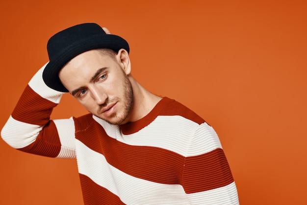 Bel homme casquettes pull rayé studio posant fashion fond rouge