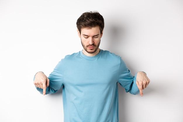 Bel homme caucasien avec barbe, vêtu d'une chemise bleue, regardant et pointant vers le bas sur une bannière de logo intéressante, debout sur fond blanc.