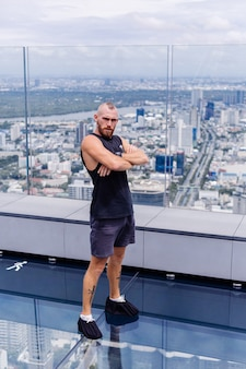 Bel homme caucasien barbu brutal sur rd plancher de verre à bangkok