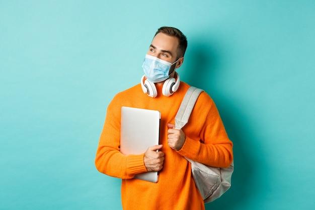 Bel homme caucasien avec un casque et un sac à dos, tenant un ordinateur portable et portant un masque médical, l'air heureux, debout sur fond bleu clair.