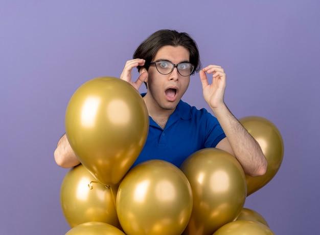 Un bel homme caucasien choqué dans des lunettes optiques se tient avec des ballons à l'hélium regardant la caméra