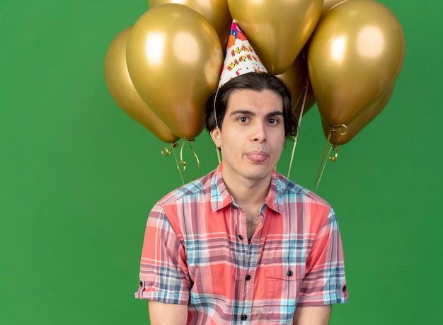 Un bel homme caucasien confiant portant une casquette d'anniversaire sort la langue et se tient devant des ballons à l'hélium