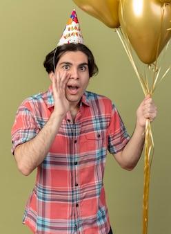 Un bel homme caucasien excité portant une casquette d'anniversaire garde la main près de la bouche et tient des ballons à l'hélium