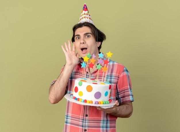 Un bel homme caucasien excité portant une casquette d'anniversaire se tient avec la main levée et tient un gâteau d'anniversaire