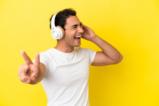Bel homme caucasien sur fond jaune isolé, écouter de la musique et chanter
