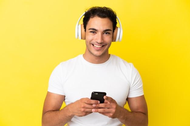Bel homme caucasien sur fond jaune isolé, écouter de la musique avec un mobile et regarder avant