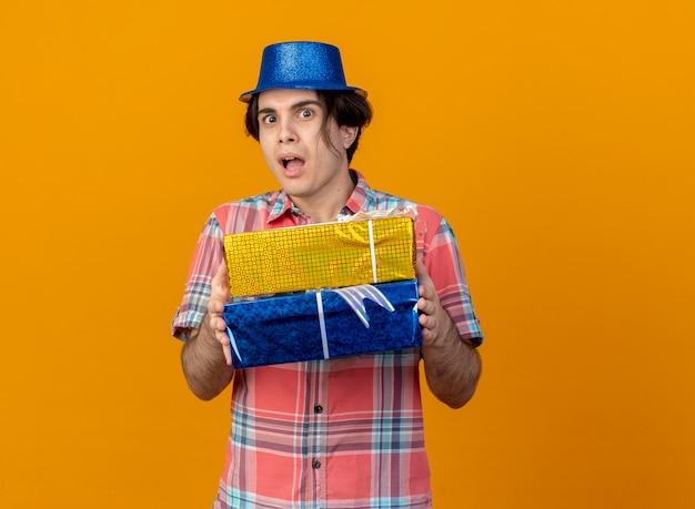 Un bel homme caucasien impressionné portant un chapeau de fête bleu tient des coffrets cadeaux