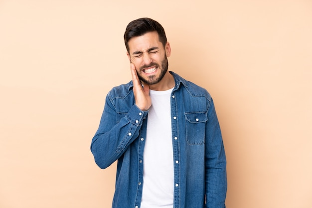 Bel homme caucasien isolé sur un mur beige avec des maux de dents
