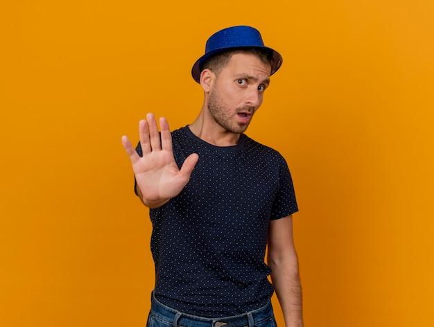 Bel homme caucasien malheureux portant des gestes de chapeau de fête bleu signe de la main d'arrêt isolé sur fond orange avec espace de copie