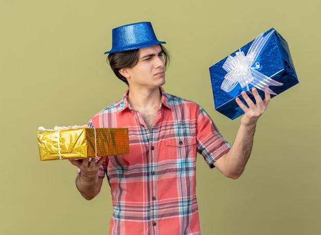 Un bel homme caucasien mécontent portant un chapeau de fête bleu tient et regarde les coffrets cadeaux