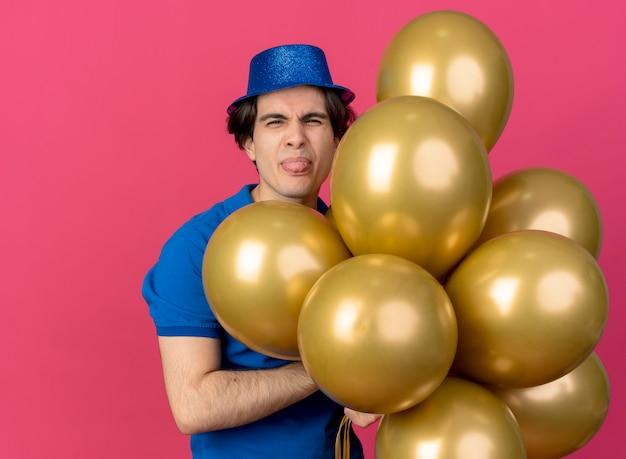 Un bel homme caucasien mécontent portant un chapeau de fête bleu tire la langue et tient des ballons à l'hélium